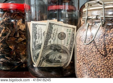 Hundred Dollar Bills In A Glass Jar Among Other Jars Of Cereal And Dried Fruit On The Shelf. Cash. K