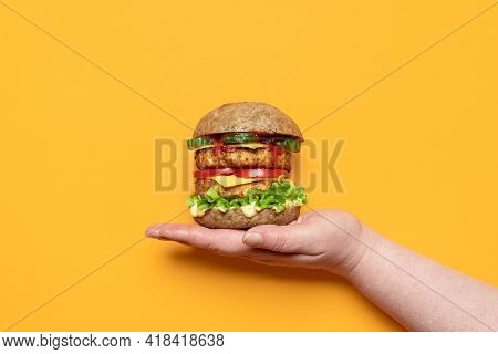 Woman's Hand Holding A Homemade Vegan Burger On An Orange Background. Veggie Burger With Soy Patties