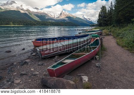 Colorful Boats By Maligne Lake, With Samson Peak, Maligne Mountain And Mount Paul In The Background.
