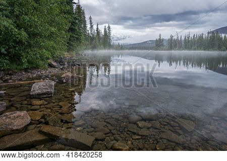 Mountains And Clouds Reflect In Water Surface Of Pyramid Lake In Canadian Rockies. Misty, Rainy Even