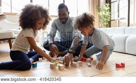 Happy Millennial Dad Enjoying Learning Playtime With Sibling Preschooler Kids