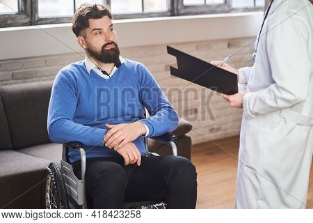 Handsome Bearded Man Sitting In A Wheelchair And Listening To A Doctor