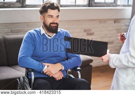 Cheerful Man In A Wheelchair Talking With A Physician