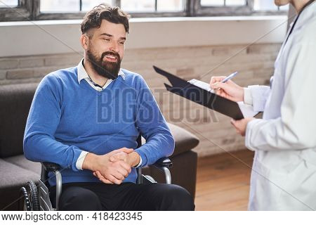 Handsome Ex-serviceman In A Wheelchair Having A Physicians Visit