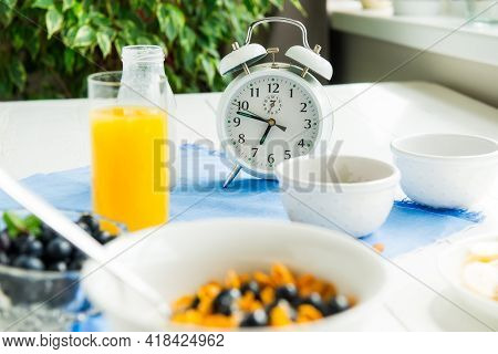 Time For Breakfast. Alarm Clock With Healthy Food. Bowl With Cereals, Nuts And Berries, Milk, Fresh