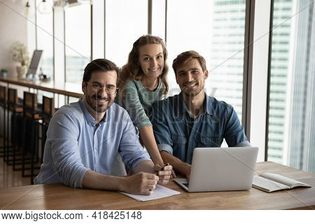 Portrait Of Smiling Diverse Businesspeople Cooperate On Computer