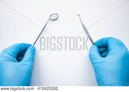 Dentist Mirror And Probe In Hands Isolated On White. Professional Dental Hygiene Cleaning Tools. Cal