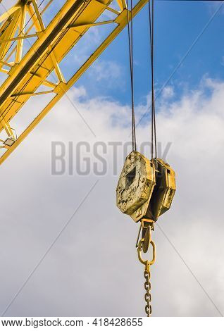 Overhead Crane Hoist Industrial Mechanism With Hook And Chain On A Background Of Blue Sky With Cloud
