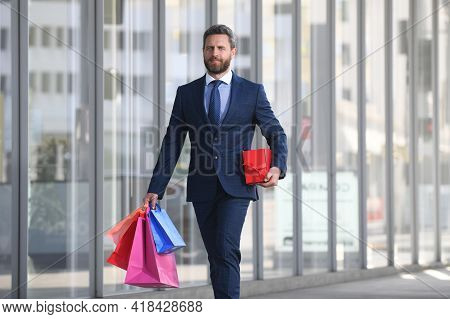 Business Man Holding Shopping Bags And Walking In Shopping Store. Shopping And Paying. Shopaholic Sh