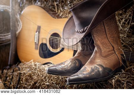 Country music festival live concert or rodeo with cowboy hat guitar and boots in barn background