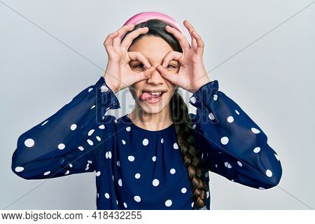 Young brunette girl wearing elegant look doing ok gesture like binoculars sticking tongue out, eyes looking through fingers. crazy expression.
