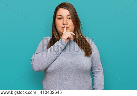 Beautiful brunette plus size woman wearing casual clothes asking to be quiet with finger on lips. silence and secret concept.