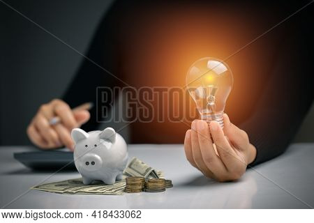 Hand Holding A Light Bulb With Piggy Bank, Dollar Bill, Coins Stack. Money Management For The Future