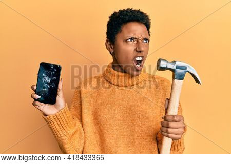 Young african american girl holding broken smartphone showing cracked screen and hammer angry and mad screaming frustrated and furious, shouting with anger. rage and aggressive concept.