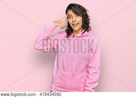 Young hispanic woman wearing casual sweatshirt smiling pointing to head with one finger, great idea or thought, good memory
