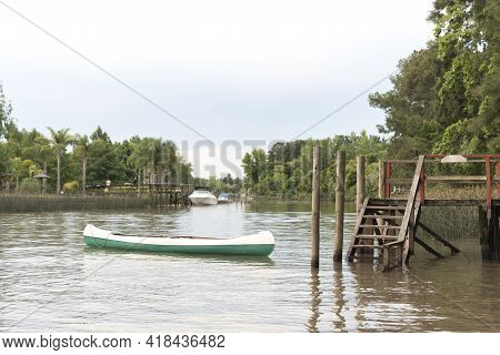 A Canoe And A Wooden Dock In A Creek In The Tigre Delta, A Quiet And Picturesque Area Of The Provinc