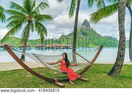 Vacation - Elegant woman relaxing in hammock on Bora Bora travel paradise during summer holidays in tropical Bora Bora, French Polynesia, Tahiti. Luxury overwater bungalow resort hotel. Travel icon