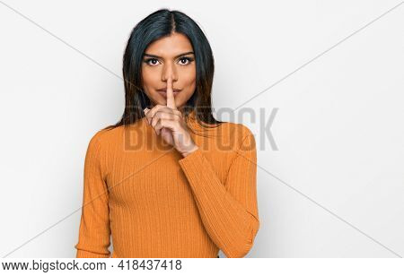 Young latin transsexual transgender woman wearing casual clothes asking to be quiet with finger on lips. silence and secret concept.
