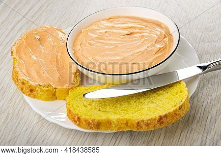White Glass Bowl With Creamy Fish Oil, Sandwich, Slices Of Cornbread, Table Knife In Plate On Wooden