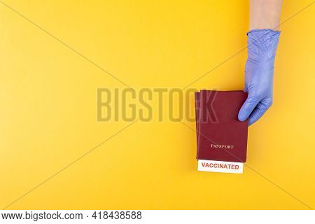 Hand In Medical Glove Holding Passport With Vaccinated Stamp On Yellow Background