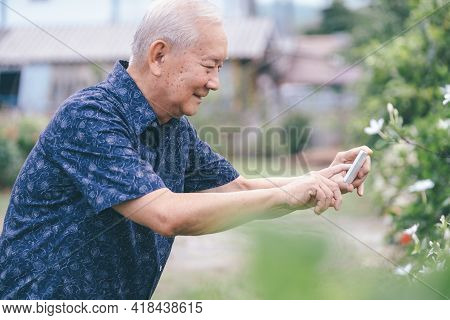 Happy Asian Senior Man Taking A Picture With Mobile Phone.