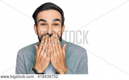 Young hispanic man wearing business clothes laughing and embarrassed giggle covering mouth with hands, gossip and scandal concept
