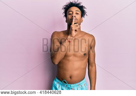 Young african american man with beard wearing swimsuit asking to be quiet with finger on lips. silence and secret concept.