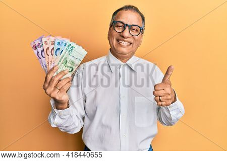 Middle age indian man holding thai baht banknotes smiling happy and positive, thumb up doing excellent and approval sign