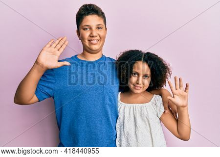 Young hispanic family of brother and sister wearing casual clothes together waiving saying hello happy and smiling, friendly welcome gesture