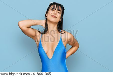 Young hispanic woman wearing swimsuit and sunglasses suffering of neck ache injury, touching neck with hand, muscular pain