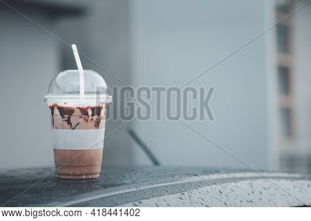 Iced Mocha Coffee On Front Roof Of Car After Raining. Close Up