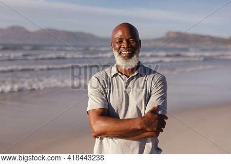 Portrait of senior african american man with arms crossed smiling while standing on the beach. travel vacation retirement lifestyle concept