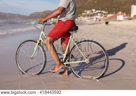 Mid section of african american man sitting on bicycle on the beach. travel vacation retirement lifestyle concept