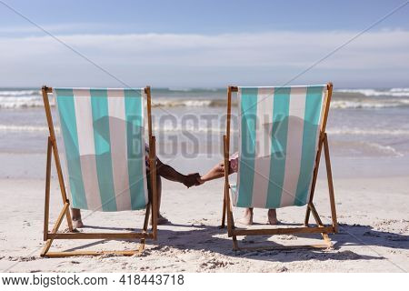 Rear view of senior african american couple holding hands while sitting on deck chairs at the beach. travel vacation retirement lifestyle concept