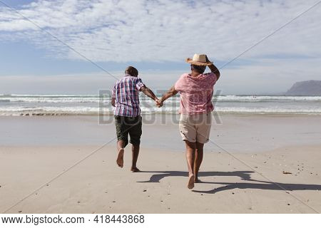 Rear view of senior african american couple holding hands running on the beach. travel vacation retirement lifestyle concept