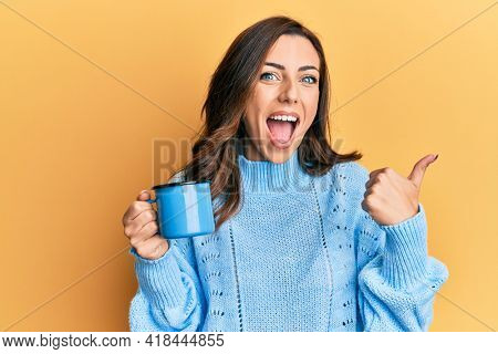 Young brunette woman holding a cup of coffee pointing thumb up to the side smiling happy with open mouth