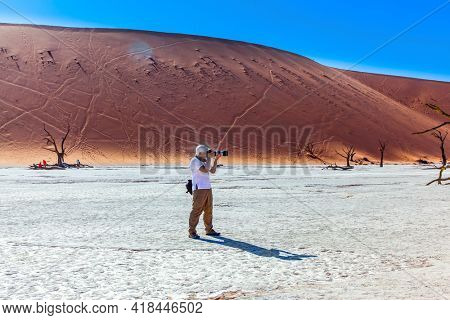 Tourist with a photo bag photographs a picturesque orange dunes. Grand trip to Africa, Namib Naukluft desert. The dry lake Sussussflay. The concept of exotic, extreme and photo tourism