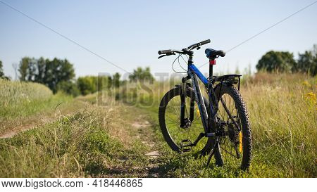 Bike Stands On In The Field. A Mountain Bike Stands On A Field Path With Green Grass. Cycling. Mount