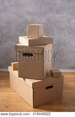 Stack of cardboard box on floor background. Cardboard boxes for moving to new home. Relocation concept in room