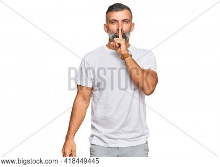 Middle age handsome man wearing casual white tshirt asking to be quiet with finger on lips. silence and secret concept.