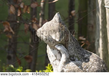 Close Up Of A Concrete Weathered Statue Of A Cat Scratching Behind Her Ear