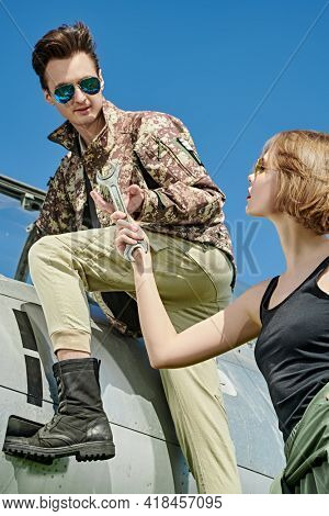 A beautiful girl helps a handsome man pilots who repairs fighter. Military aircraft. Military fashion.