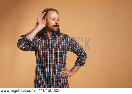 Bearded ginger focused man gesturing and eavesdropping isolated over beige background