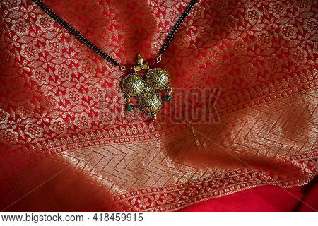 Stock Photo Of Beautiful Fancy Golden Mangalsutra With Black Pearl Chain On Beautiful Red And Golden