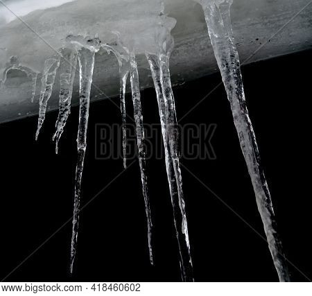 Long Pointy Icicles From Frozen Water Hanging Of The Side Of A Roof.