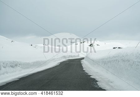 Road Through A Mountain Pass With Deep Snow Towering Up On Both Sides.