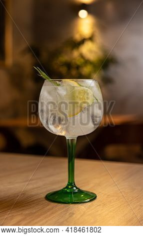 Cold Refreshing Tonic Water With Ice Decorated With Rosemary And Lemon