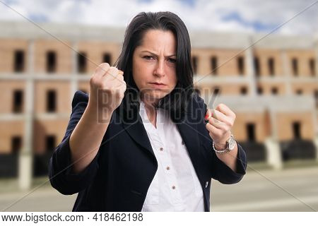 Angry Businesswoman In Smart Casual Formal Suit Showing Fighting Fists As Aggressive Gesture On Reno