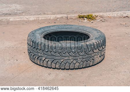 Thrown Out On A Deserted Road, An Old, Worn-out Winter Tire From A Car Wheel