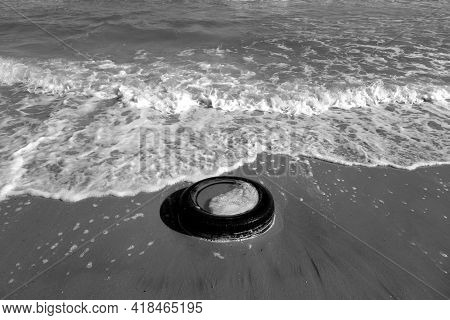 Used Car Tyre On The Sea Beach In Black And White. Ecological And Environment Isues.